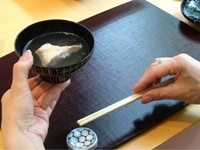 右手で箸を持ち上げる