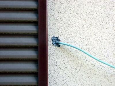 コンセントカバーに穴を開け通したLANケーブルとコネクタを室外に出した