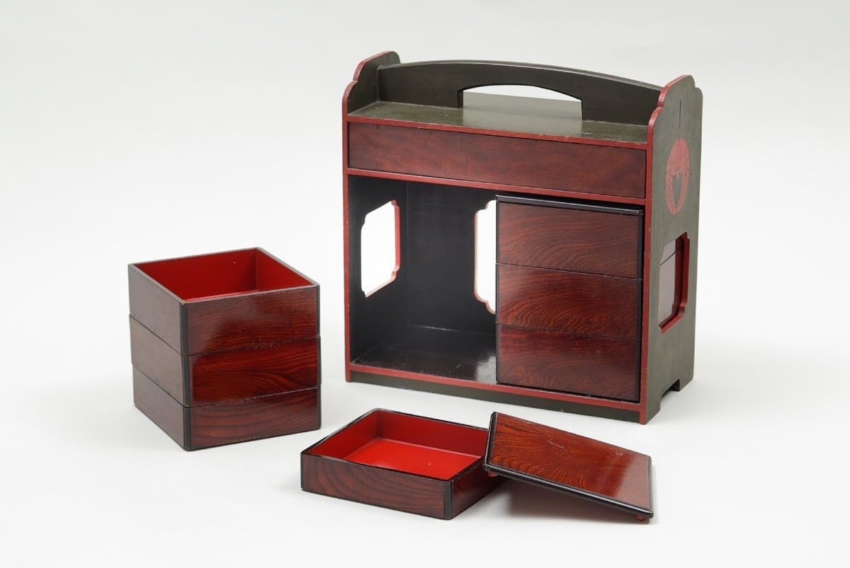 A typical lacquered wooden bento box from the Azuchi-Momoyama period (ca. 16th century). The box shows a total of 6 small compartments for various types of food. This particular bento set also has a main compartment larger than the others. The box has a handle on top.