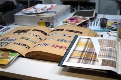 布見本帳もカラフル。まわりには絵の具とパレットで試行錯誤の跡も。