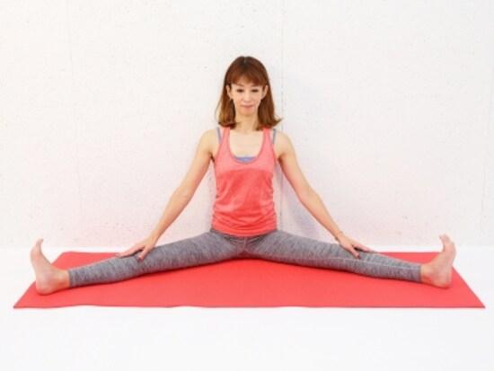 動作1 両脚を大きく開き、背骨をまっすぐ伸ばします。