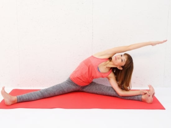 動作1 脚を大きく開き、上体を左方向に倒します。右の脇腹をゆっくりストレッチ。