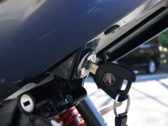 鍵が刺さっているのがシートの開閉装置。左下にあるのがヘルメットロック