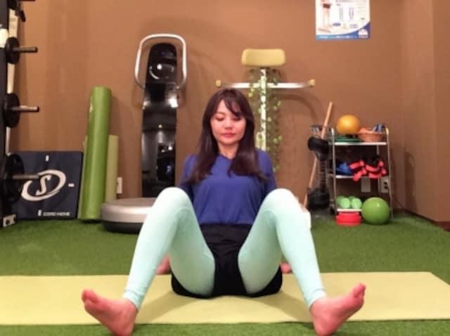 動作1 足を肩幅より広く開き、つま先を床から上げて踵で床を押すようにする。