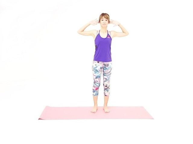 バランス体幹エクササイズ1 脚を腰幅に開き両手を耳に添えます。