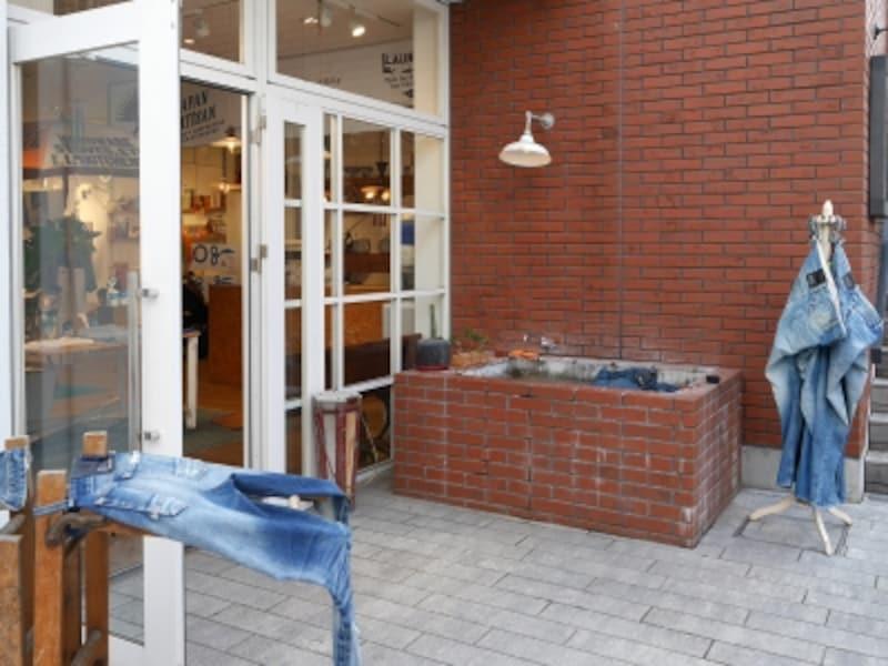 「DENHAM(デンハム、E棟1、2階)」では、入口横で「洗い加工」する様子が見られます(2018年6月17日撮影)