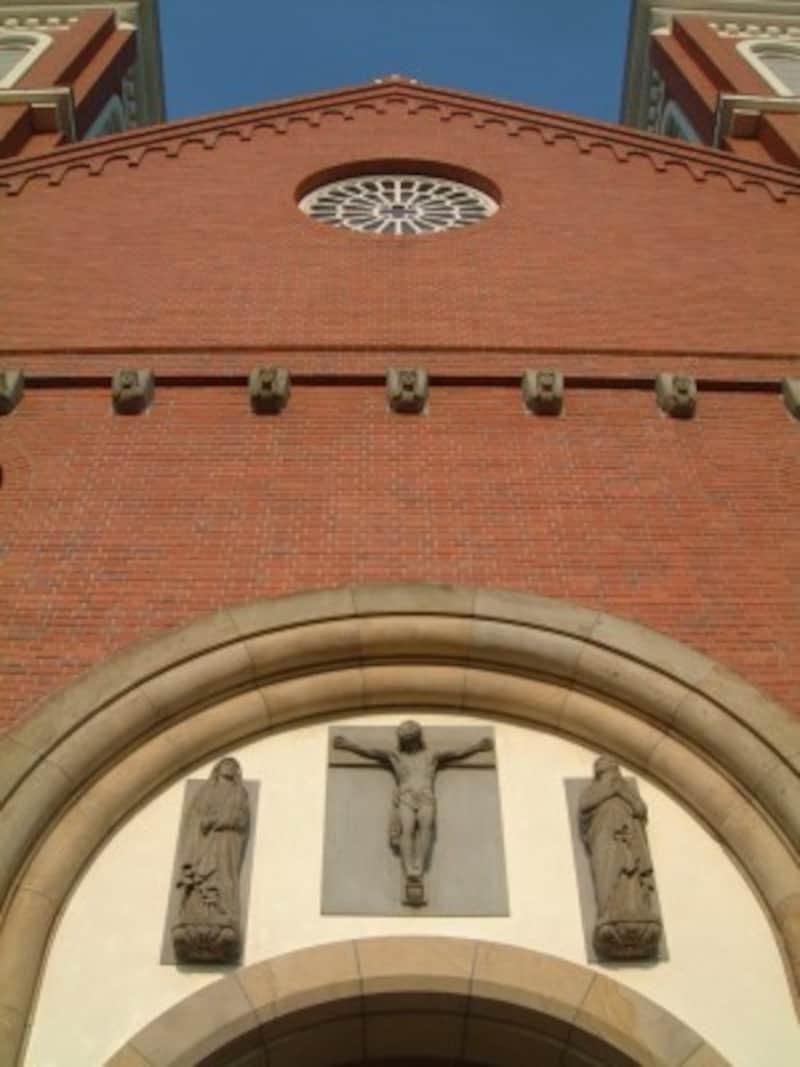 浦上天主堂(2)/正面に埋め込まれたキリスト石像と聖マリア像、聖ヨハネ像