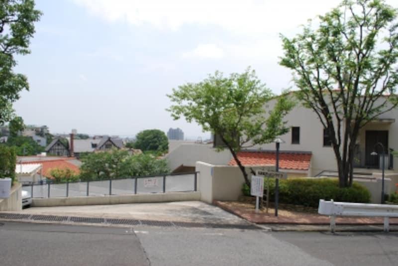 斜面地に建つ分譲マンション。オレンジ色の屋根が眼下に見える。
