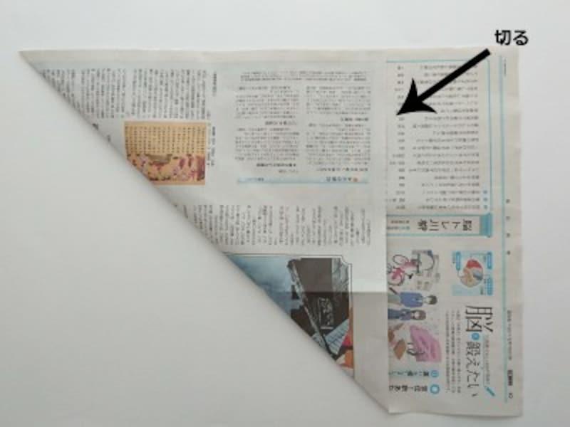 新聞紙を斜め上に折り上げる