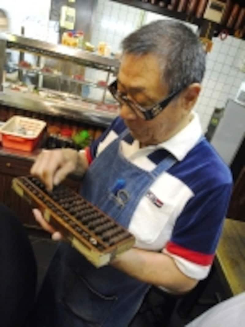 おしゃれな黒ぶち眼鏡がトレードマークの3代目、山田弘さん(71歳)。会計はそろばん、しかもこれまた年季入りすぎ!