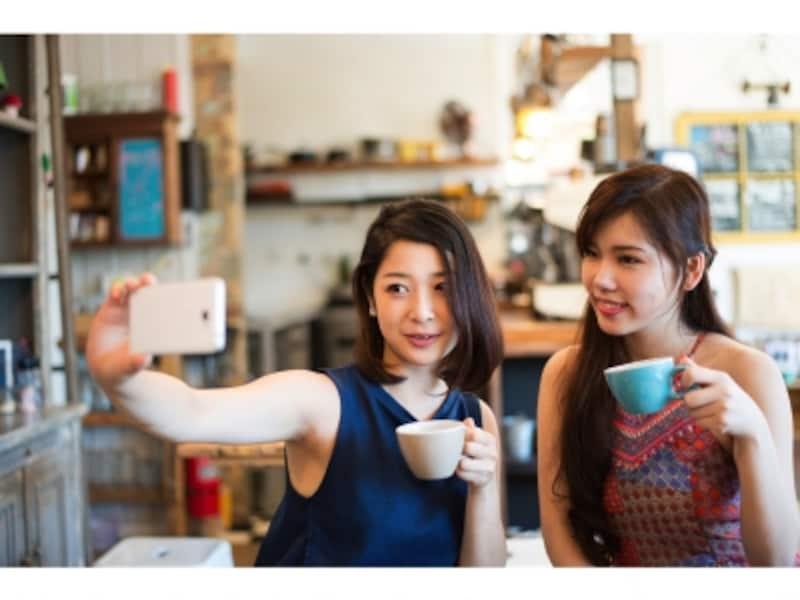 白いスマートフォンで自撮りする2人の女性