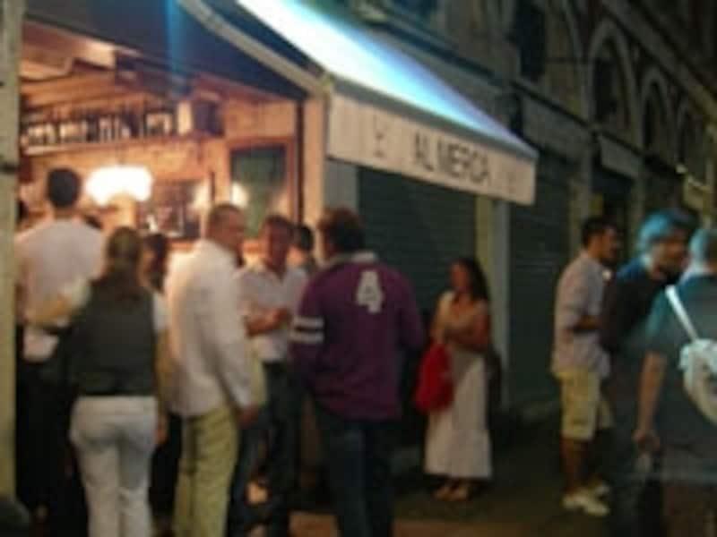 店の外でワイン片手に賑わう人々