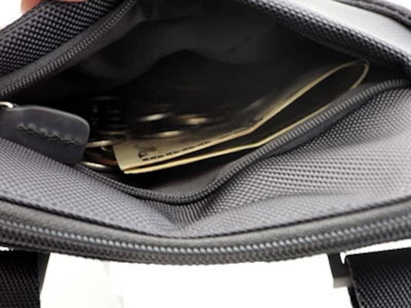 上部のファスナーポケットを財布代わりに使う。