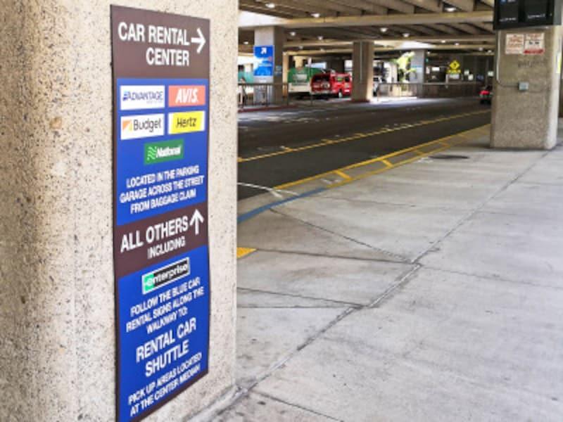 個人出口を出て右方向へ歩き、柱番号EとFの間にある横断歩道を渡ってカー・レンタル・センター内の各社カウンターへ