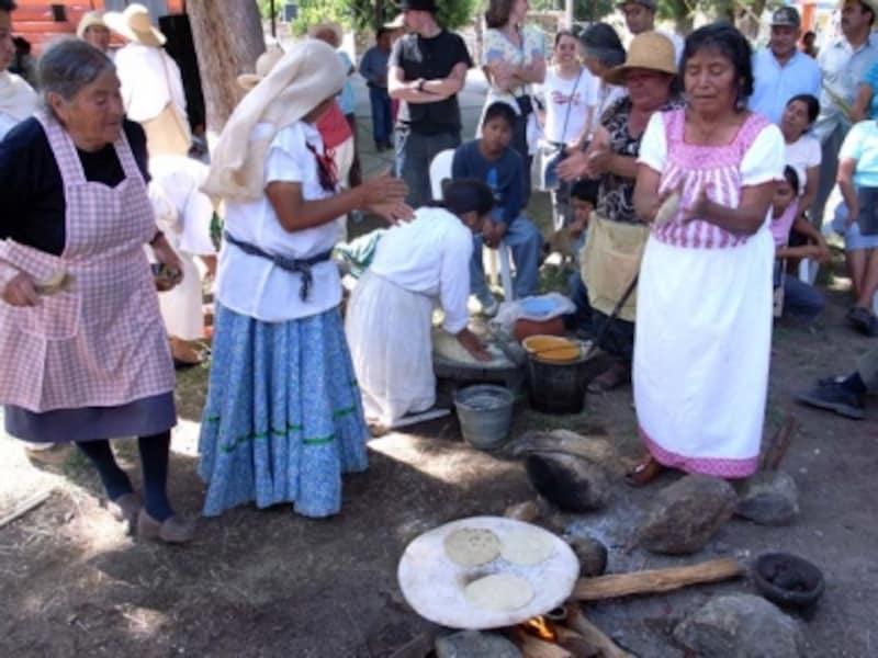 昔ながらのやり方で、手でたたくようにトルティージャを成形する女性たち