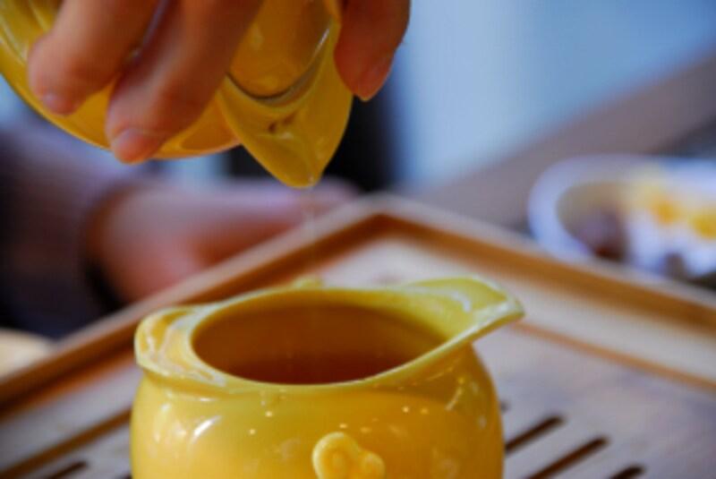 黄色い茶器で茶を淹れる画像