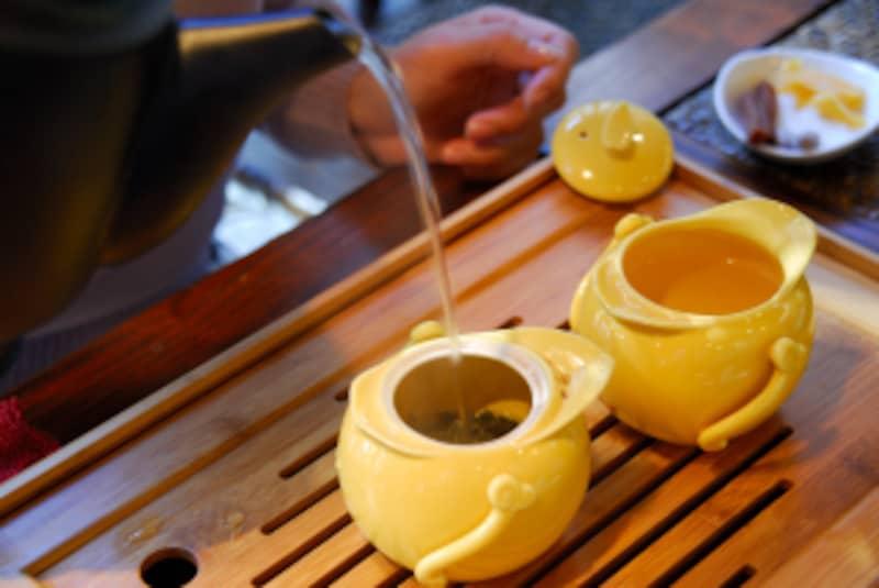 黄色い茶器に湯を注ぐ画像