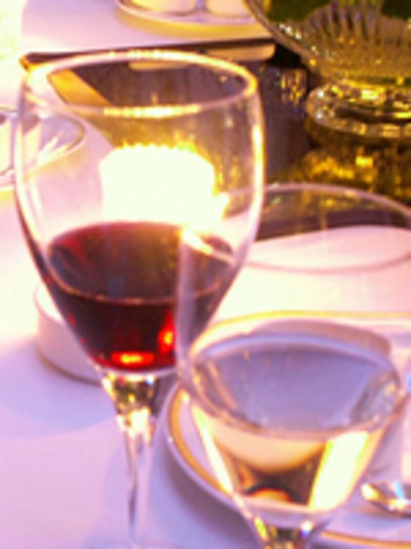 赤白のワインが入ったグラスの向こうに灯りが見える