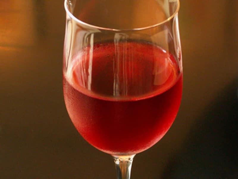 ワイングラスに入った透明で紅色のキール