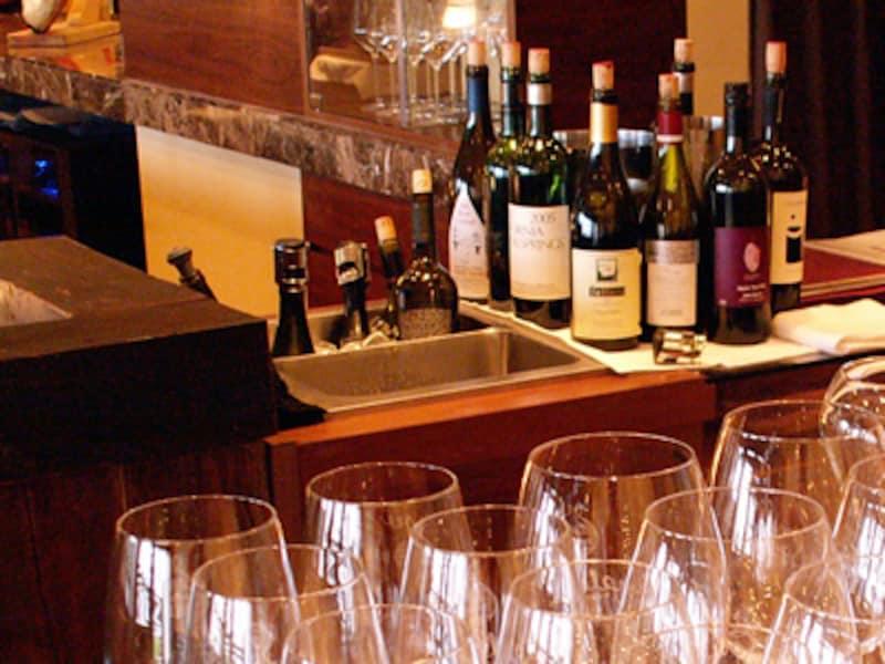 手前に数多く並ぶワイングラス、奥には抜栓してコルクやストッパーでふたをしたワインボトルが林立する