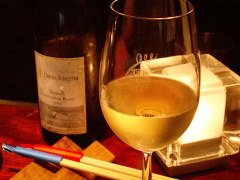 キャンドルの灯りと白ワインのグラス、箸置きと箸のセッティング