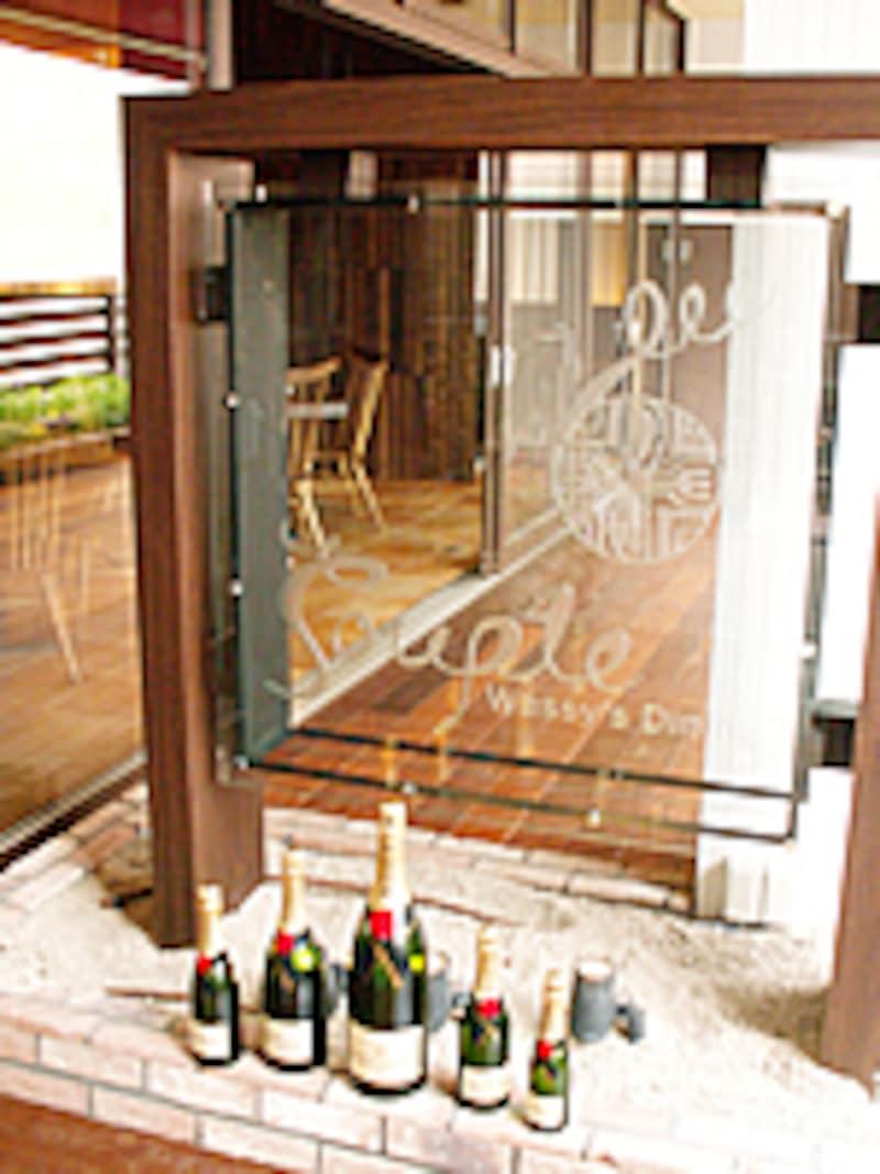 木製の枠に固定されたガラスの店名プレート