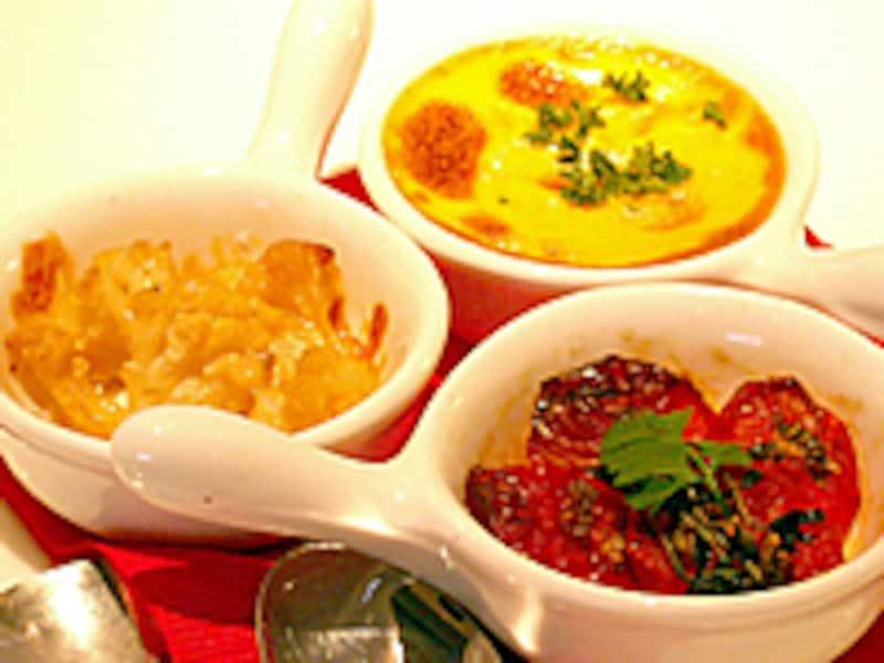 3つのミニフライパン型陶器皿に赤・黄・茶色の料理が盛り付けられる