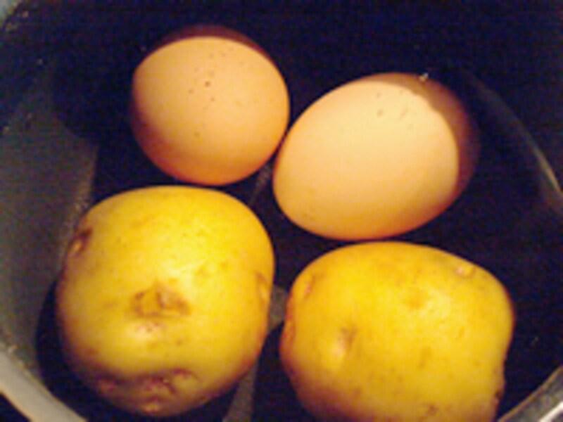 黒い鍋の中の水に赤玉の卵とジャガイモが2つずつ沈んでいる