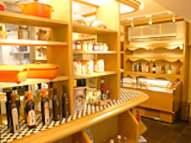 ドアを開けた1Fのエントランスには、使われているプロの食材が並んだ棚と厨房。厨房からは「いらっしゃいませ!」の声が