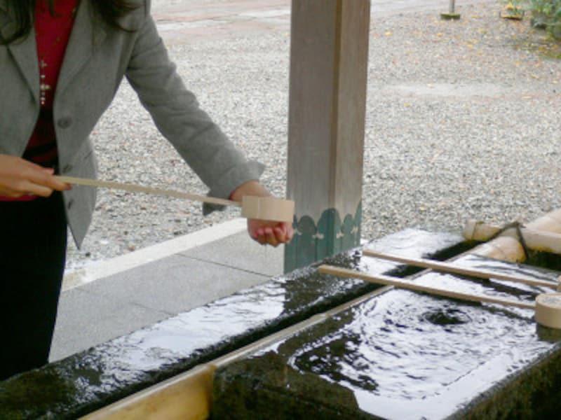 手水のやり方・手水舎での作法1:右手で柄杓を持って水を汲み、左手にかける