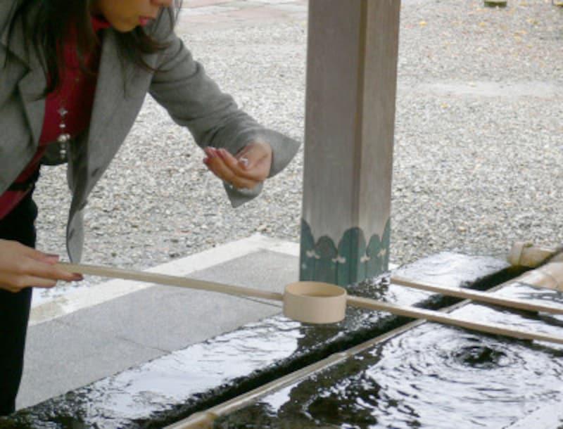 手水のやり方・手水舎での作法3:再び柄杓を右手に持ち替え、左の掌に水を受けて口をすすぐ