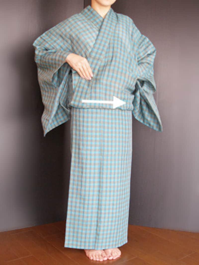 衣着付け17:衿が崩れぬよう右手で押さえながら、身八つ口から左手を入れ、前のおはしょりの中に手を入れて、衿の所から脇へ整えていきます