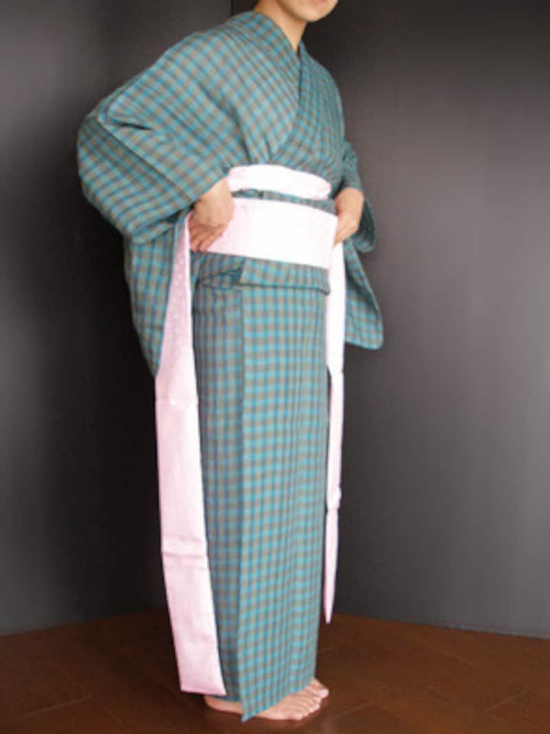 浴衣着付け29:両手で伊達締めを持って当て、伊達締めの下端でおはしょりを引き上げるように整えながら……