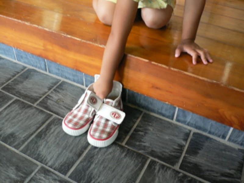 靴の脱ぎ方3:靴の向きを変え、家人から遠いほう(またはシューズボックス側)の隅に寄せて置きます。