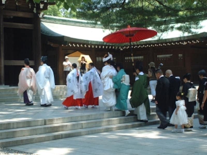 明治神宮での神前式の様子。鮮やかな緑の中、挙式会場となる参殿に向かいます。参列者も列をなして花婿花嫁につづきます