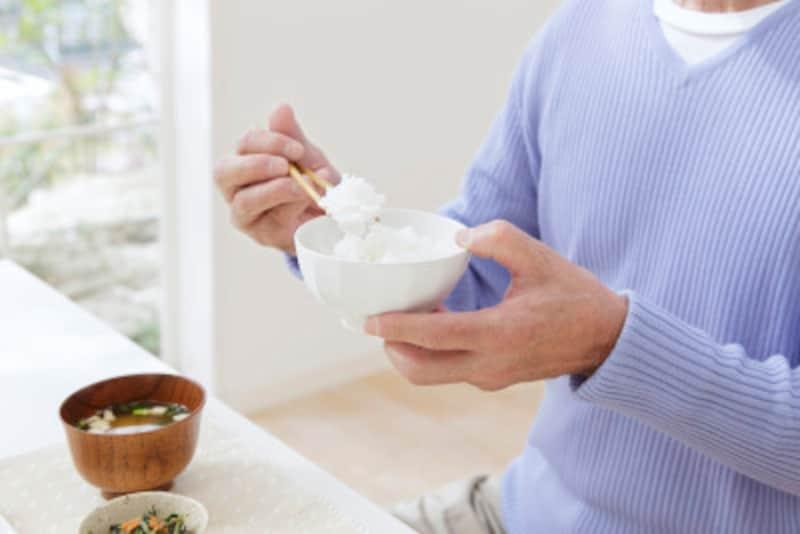いかなる時も姿勢を正し、行儀良く食べる男性/作業のように淡々と、料理を口に運ぶ男性