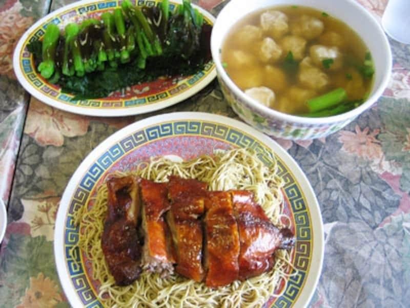 汁なし麺の上にローストダックをのせた「香港ヌードルハウス」のトスヌードル。別注の青菜やテーブルの上の酢などの調味料を混ぜて食べる