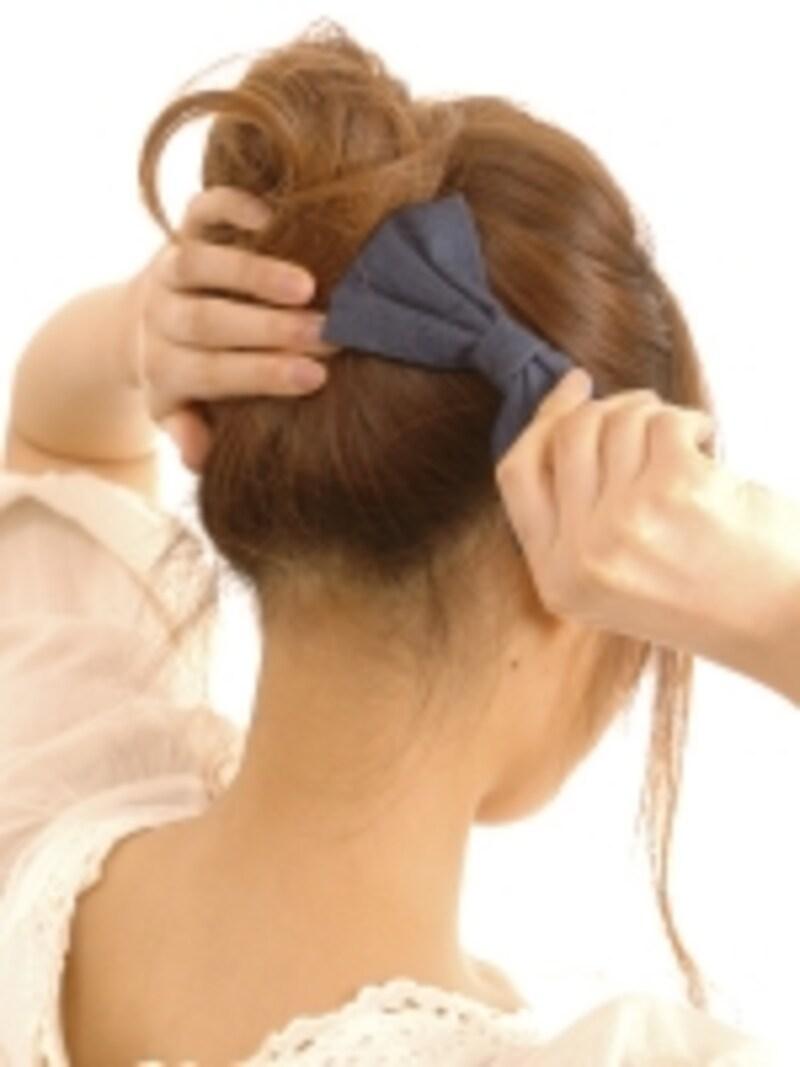 ねじり上げた毛束がたるまないよう、片手で押えながらクリップを