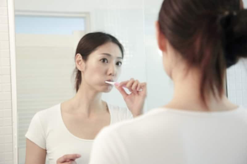 鏡をみて歯を磨く女性