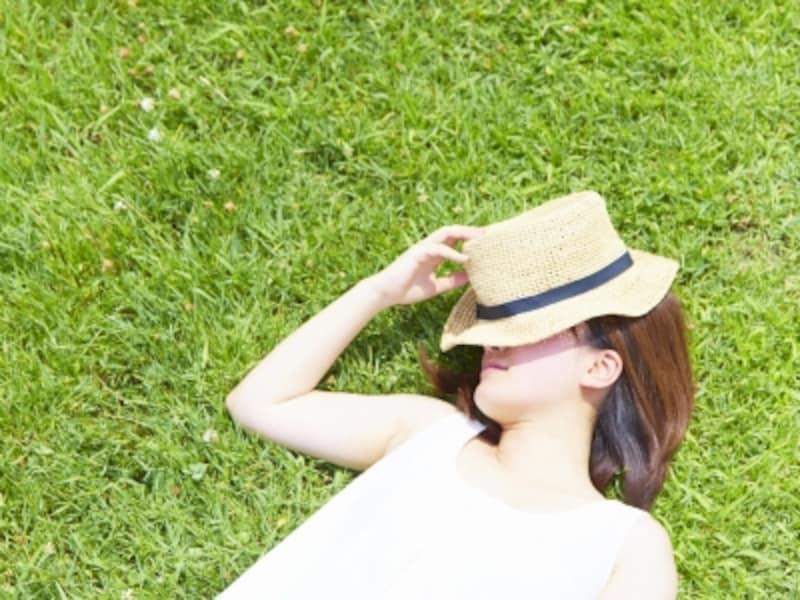 太陽の下で寝転ぶ女性