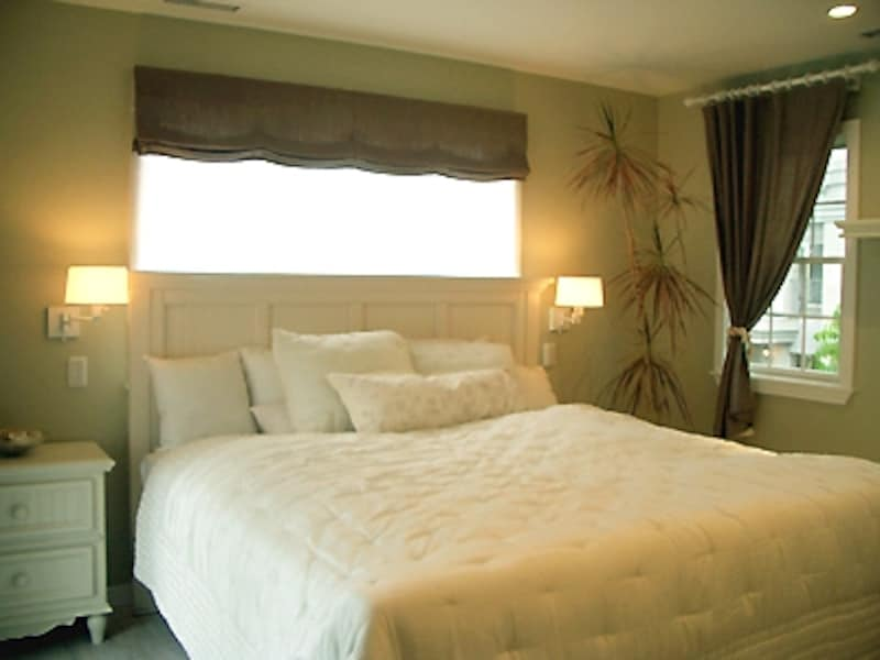 落ち着いたグリーン系の壁はドライウォール仕上げ。キングサイズのベッドの両脇にはそれぞれ枕元灯のスイッチがある。