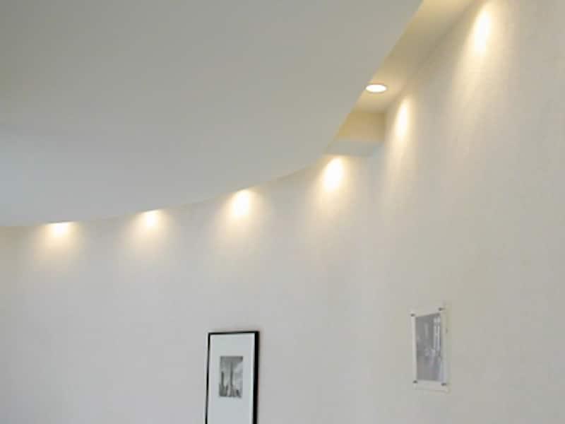 壁際の天井にダウンライトを埋め込み壁面をライトアップしているモデルハウス(三菱地所ホーム)