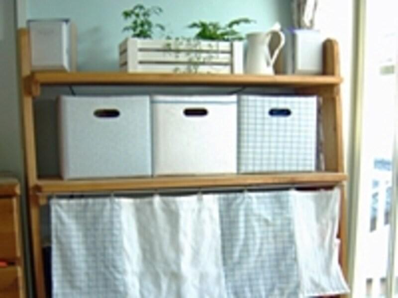 手作りの本棚。ブルーの布を張った手作りの収納ボックスが並べてある。