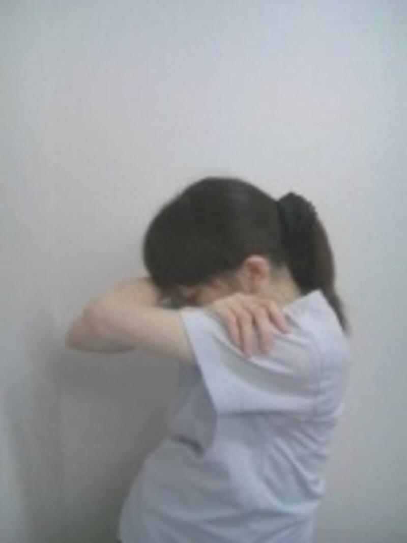 頭を下げ両肘を腕ごと前方へ動かし、上背部と首後面をストレッチします