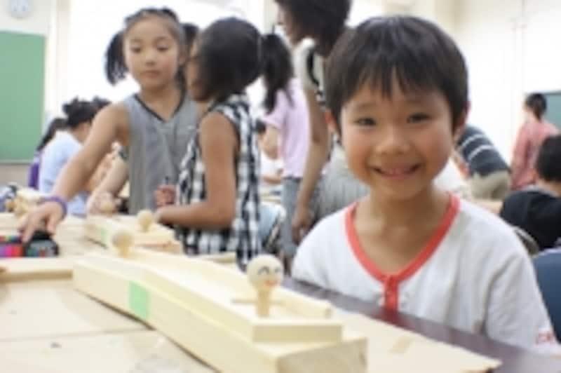 自分で作った木のおもちゃを前に大満足の笑顔!