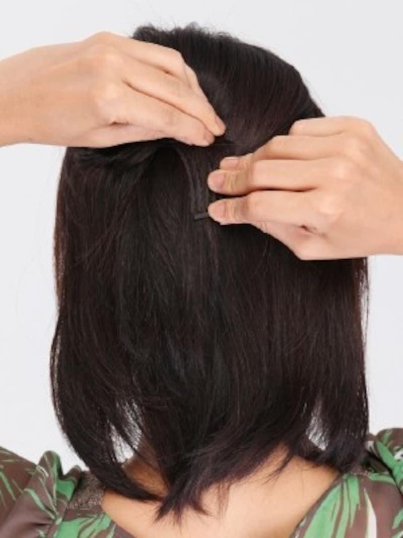 3.目立ちにくい黒のツヤ消しコームを、ねじった髪の下から差し込みます。