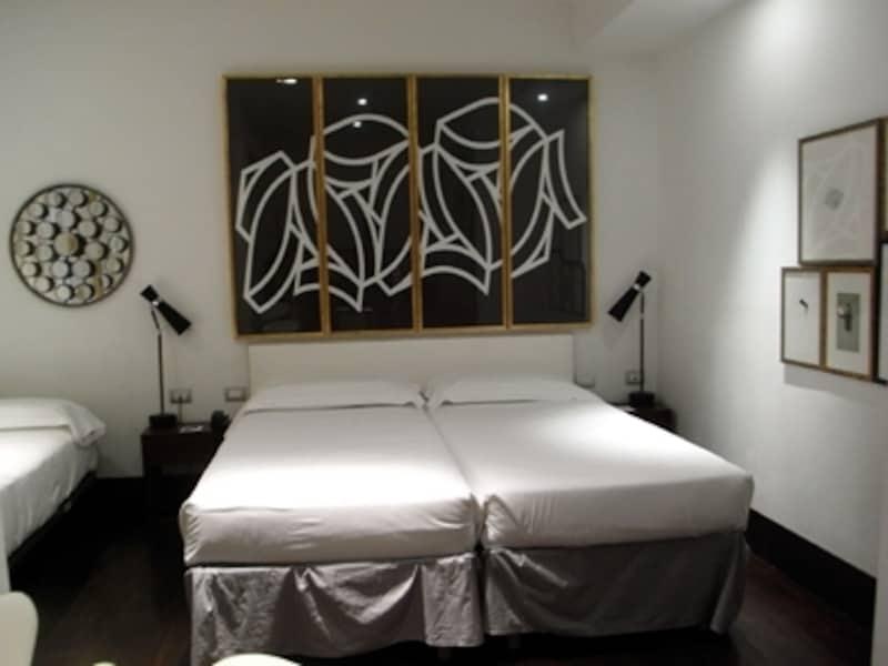 ベッドヘッドいっぱいに飾られたモノクロのモダンアートが印象的なゲストルーム