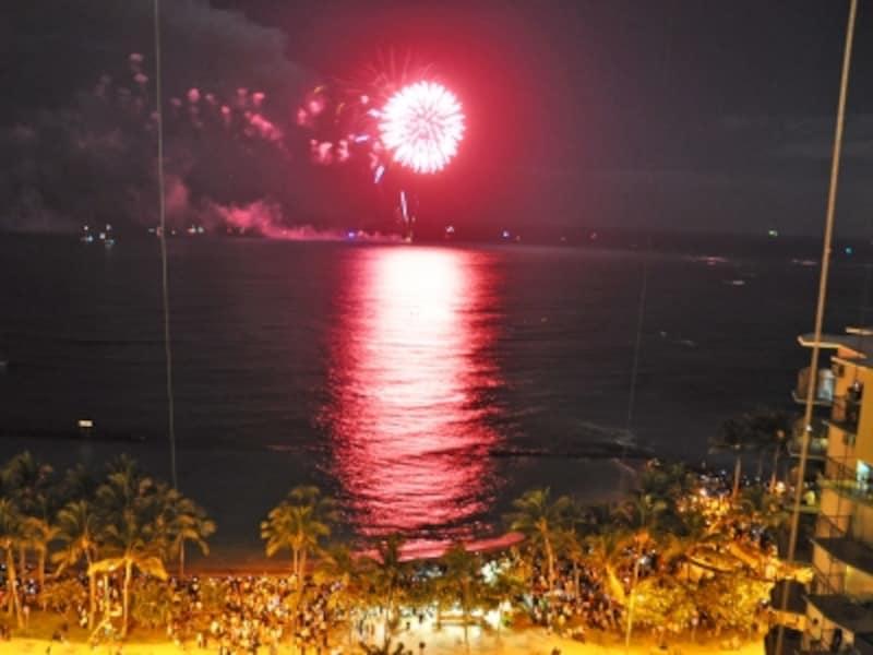 カウントダウン花火を見学する旅行者でいっぱいになる深夜のワイキキビーチ