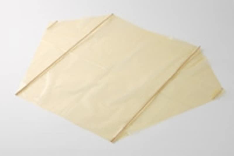 2.写真のようにポリ袋に竹ひご2本をセロテープで固定します。ポリ袋の両端にはつまようじ2本をそれぞれセロテープで貼り付けます。