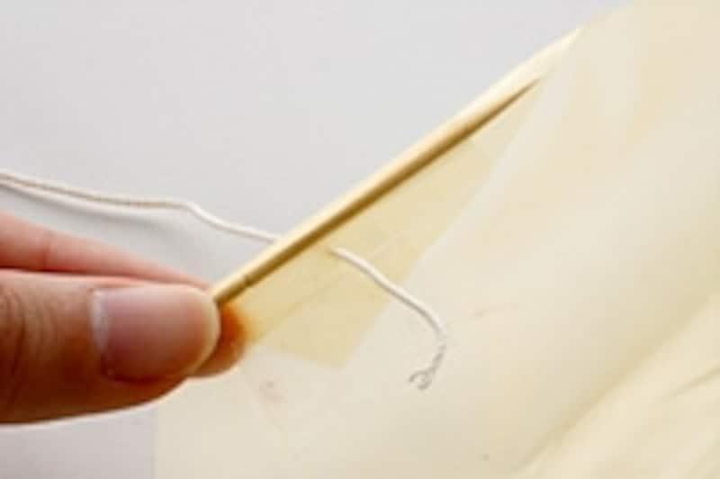 3.つまようじの部分を軸に端を折り返し、穴を開けます。たこ糸(サンプルの場合、160cm)を穴に通して、結びつけておきます。もう片方も同様にたこ糸を通して結びます